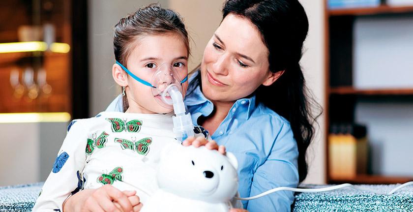 zena pomaze detetu oko inhaliranja pedijatrijskim inhalatorom